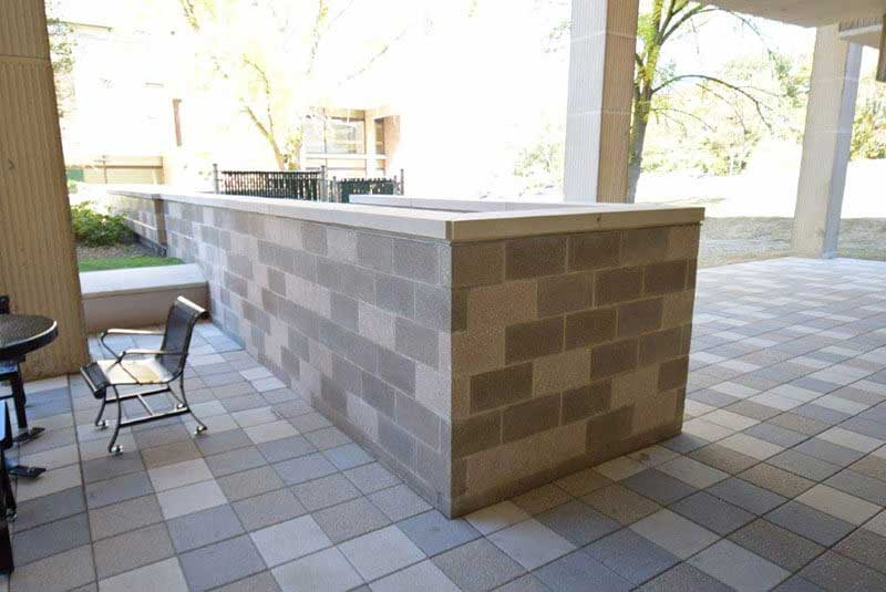 After- light gray stone has been stained to blend with a custom mocha color. The block background was stained, but the aggregate, or rock speckles in each block remain unchanged just as the owner requested.