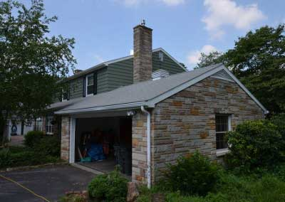 Before- original stone is a stark contrast from the sage green siding and black shutters on the remodeled home.