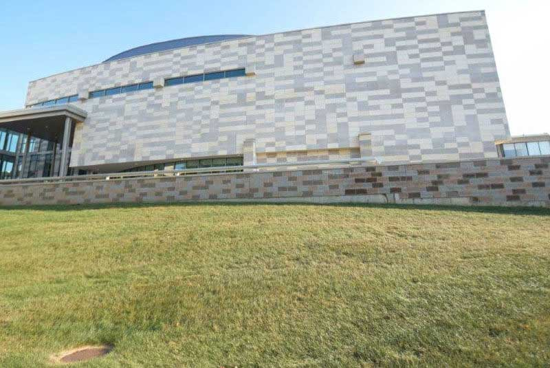 Before, darker gray limestone on building and light gray block on retaining wall make a checker board effect