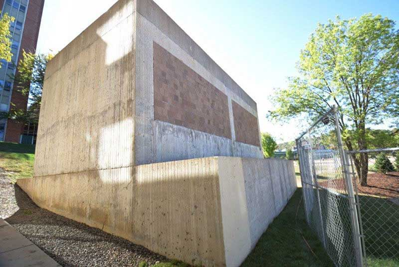 Before, ribbed concrete panels, soiled, clay colored block, efflorescence, and rain stains