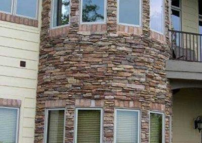 After- stone colors are all added back to the base of the home, fixing pressure wash damage and red clay soil stains