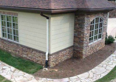 After- all stone is corrected around the entire base of the home, outdoor kitchen and attached garage with amazing results.
