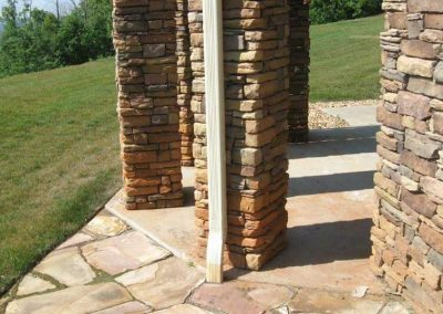 Before- red clay soil accumulated during construction damaged the stone all around the base of this home.