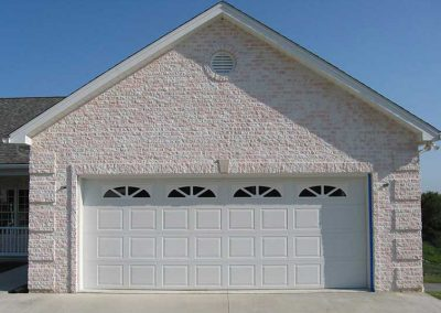 "Before- bright pink and white split-face concrete ""brick"" stands out in a neighborhood of muted and natural colors."