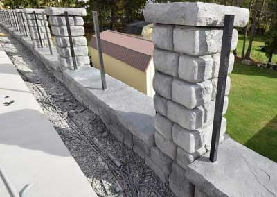 Before: Limestone pattern retaining wall install is complete, prepped and ready for custom color