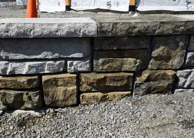 Redi-Rock Stained to Look Like Natural Stone Custom 6-Color Sample Panel Next to Uncolored Concrete